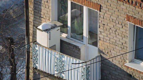 старый холодильник на открытом балконе